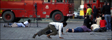 Bystanders duck as gunfire is heard at the Taj Mahal Palace hotel (27 November 2008)