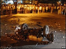 People stand by the remains of an exploded vehicle in Mumbai, India (26/11/08)