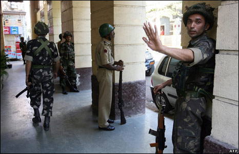 Soldiers watch the Taj Mahal Palace hotel, Mumbai, 27 November 2008