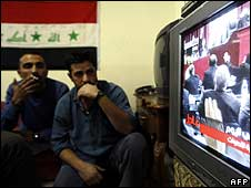 Two men in Baghdad watch the vote on television
