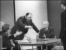 Richard Dimbleby pointing as Labour Party leader Harold Wilson and Robin Day sit around a table in the Panorama studio