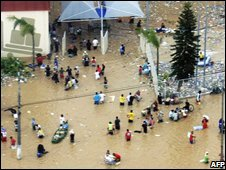 People in flood waters of the Itajay river in Santa Catarina, Brazil