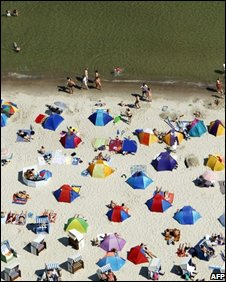 Holiday makers on beach, AFP