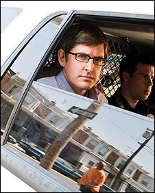 Louis Theroux travels in a police car