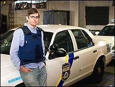 Louis Theroux stands next to a police car