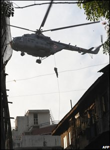An Indian National Security Guard commando abseils from a helicopter onto the rooftop of Nariman House in Mumbai, 28 November 2008