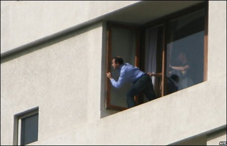 A hostage peeks from a window of the Oberoi-Trident hotel in Mumbai, 28 November 2008
