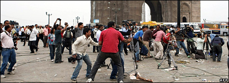 Journalists and bystanders take cover after shots are fired at them from the Taj Mahal Palace hotel (28 November 2008)
