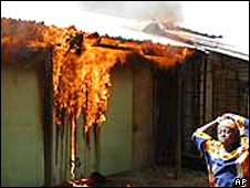 Woman running past a burning building in Yelwa, Plateau State in 2004