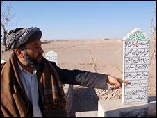 Hajji Gul Ahmed points to graves