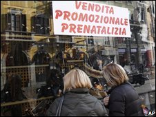 Women look at a shop window in Milan
