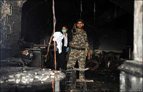 An Indian soldier stands in a charred room at the Taj Mahal hotel