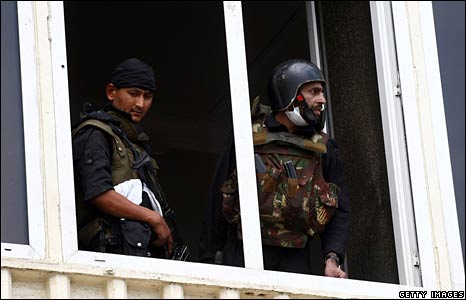 Two commandos look from one of the windows at the Taj Hotel