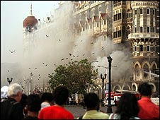 Locals look at a fire as it burns at Taj Mahal Palace