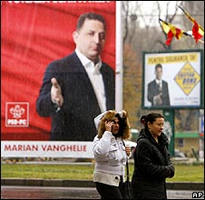 Women walk in front of electoral posters downtown Bucharest, Romania
