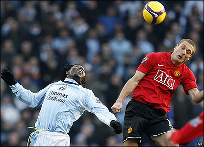 Manchester City's Benjani rises to challenge Nemanja Vidic