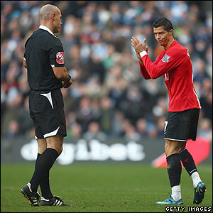 United's Cristiano Ronaldo reacts after being booked by referee Howard Webb