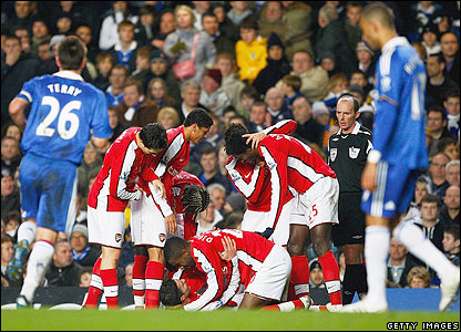Van Persie is mobbed by his Arsenal team-mates after scoring the winner