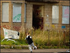 Boy playing football in boarded-up street