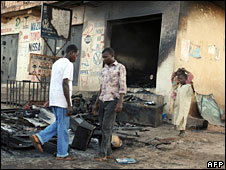 People walk past burnt-out shops in Jos (November 2008)