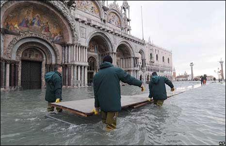 Emergency workers in St Mark's Square move boards which are usually used to create walkways