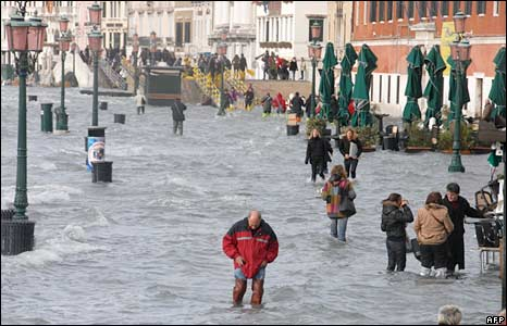 People walk on a flooded quay of the Grand Canal