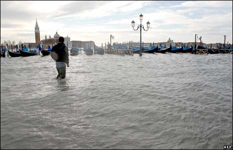A man wades through water in Venice