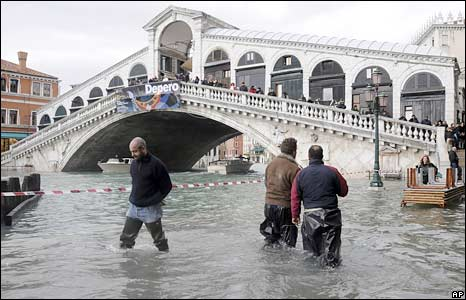 People wade through high water by the Rialto Bridge