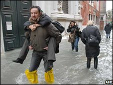 A man carries a woman on a flooded street in Venice