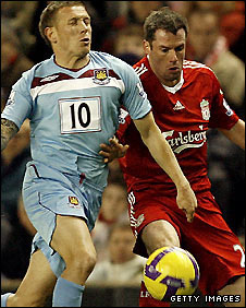 Craig Bellamy is challenged by Jamie Carragher