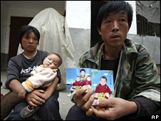 Li Xiaoquan (right) holds up a photo of his twin daughters at his home near Runan in Henan province. One of them died from kidney failure (19 October 2008)