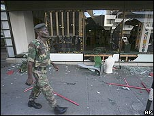 Zimbabwean soldier walks past a looted shop