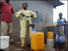 Young Ghanaian working a water pump