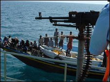 Yemeni coast guard manning a machine gun as a Yemeni fishing boat passes by during a patrol in the Gulf of Aden
