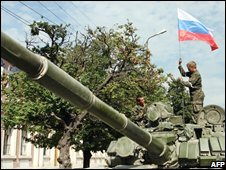 Russian soldiers place a Russian flag atop their tank in the South Ossetian town of Tskhinvali