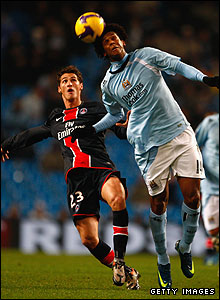 Manchester City striker Jo (r) heads away from Paris St Germain's Jeremy Clement