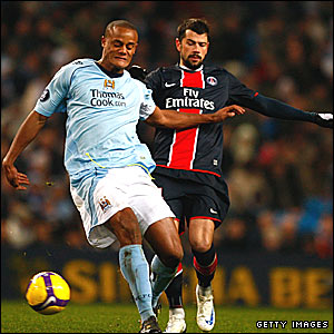 Manchester City's Vincent Kompany is challenged by Mateja Kezman