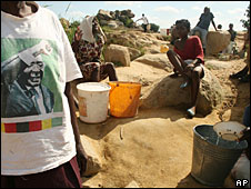 A man wearing a T-shirt showing President Robert Mugabe stands by as people take water from a well in Harare, 26 November 2008