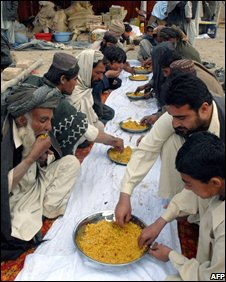 Pakistan earthquake survivors eat food distributed by Jamaat-ud-Dawa activists in November 2008