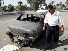 An Iraqi traffic policeman inspects a car destroyed in the Blackwater incident in September 2007