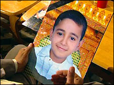 Mohammed al-Kinana holds a picture of his son, who died in the shooting