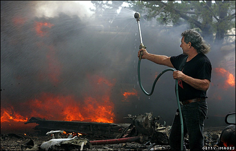Local resident attempts to fight the fire with a hose