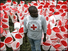 A Red Cross worker waits to distribute buckets to displaced people