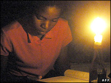 A student in Zimbabwe studying by candlelight