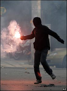 A youth throws a flare at riot police in Athens on 9 December 2008