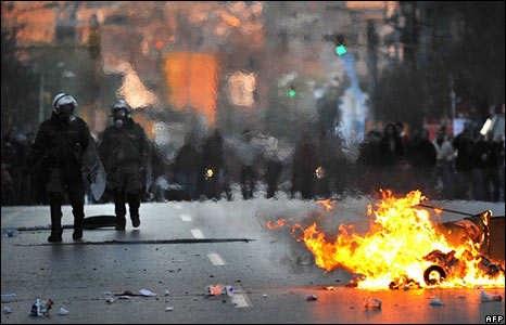Police walk past a burning barricade in the city of Thessaloniki on 9 December 2008