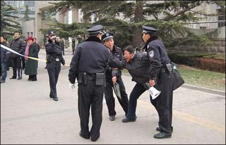 Police detain a human rights protester outside the foreign ministry in Beijing on Wednesday