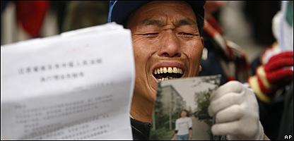 Manifestante denuncia supuestos abusos gubernamentales en Pekín durante una protesta a propósito del 60 aniversario de los DD.HH.