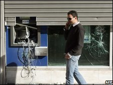 A person walks past a damaged bank in Athens
