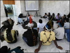 Indians of Amazonian tribes watch the court's session on a screen